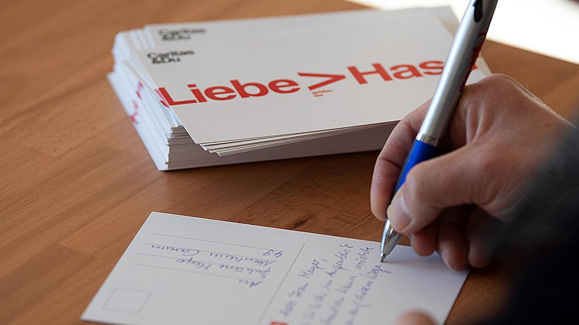 Ein Mensch schreibt eine Postkarte