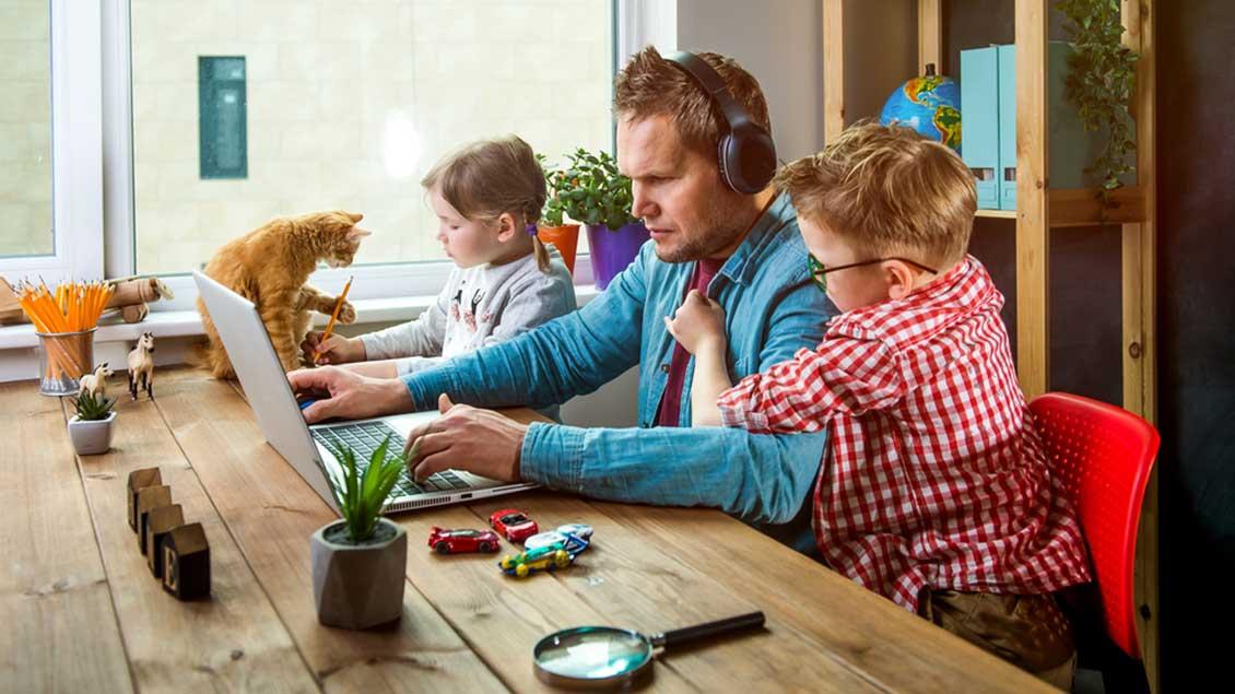 Mann mit Kindern beim Homeoffice