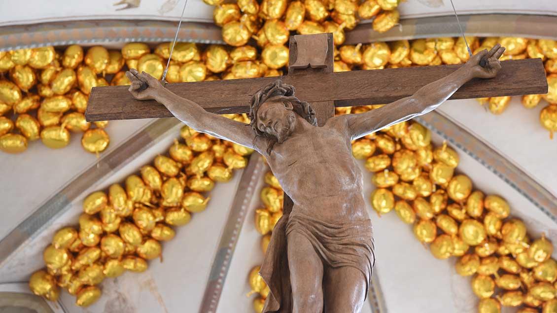 Kreuz vor goldenen Ballons