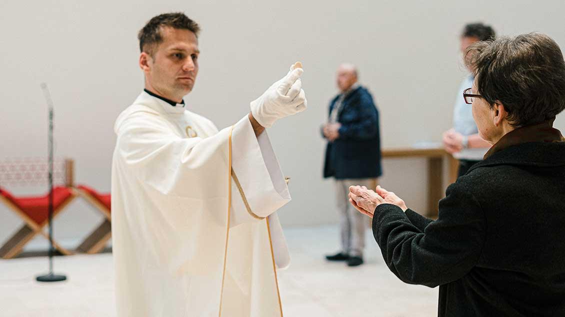 Priester spendet mit Handschuhen die Kommunion