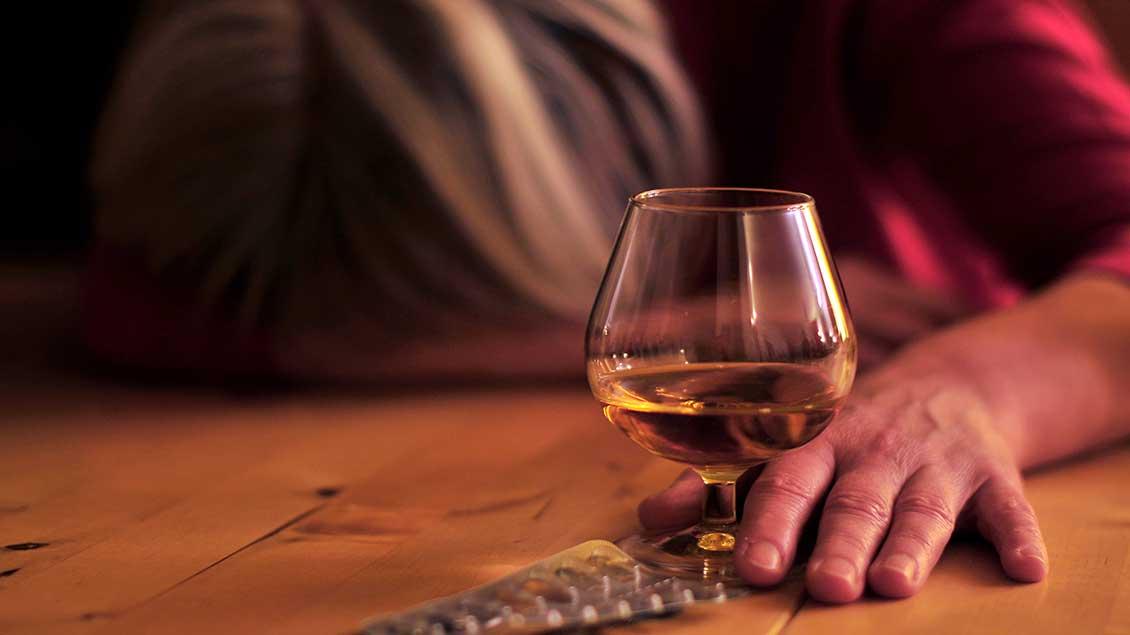 Mensch vor einem Glas mit Alkohol und einer Packung Tabletten.