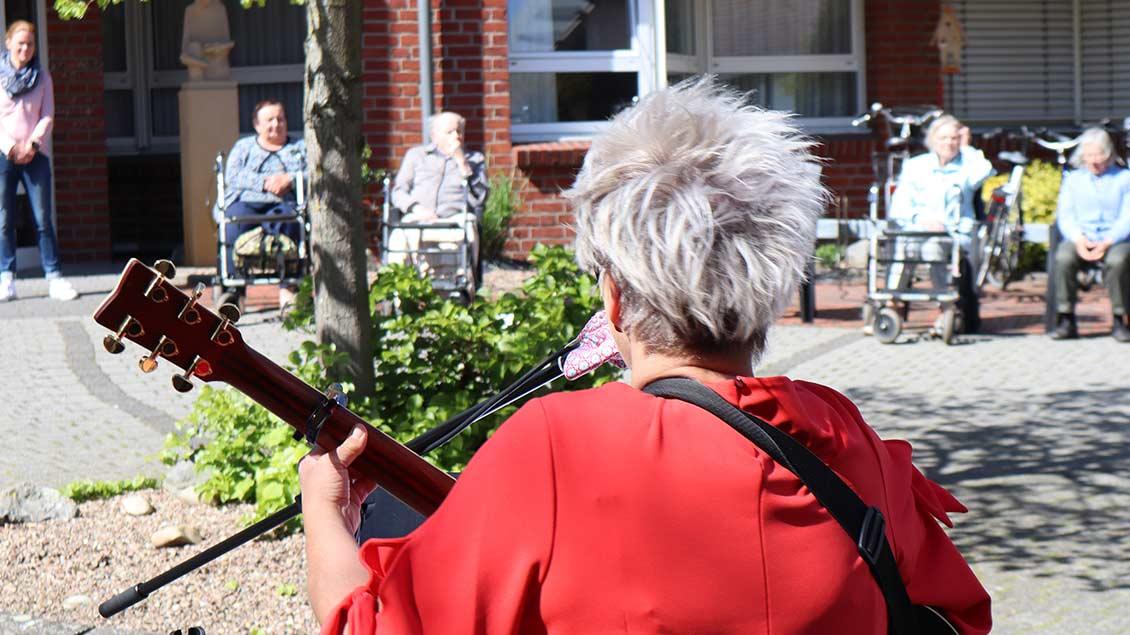 Hobbymusikerin Heike Bruns mit ihrer Gitarre vor dem Lohner Altenheim St. Elisabeth-Haus. Foto: Michael Rottmann