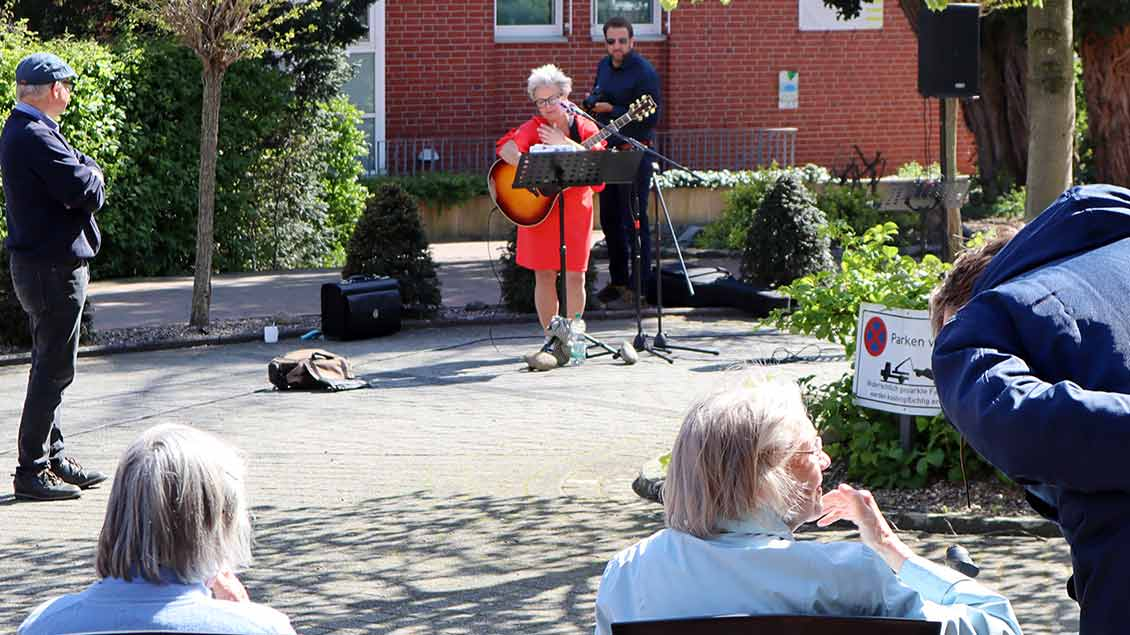 In angemssenem Sicherheitsabstand trägt Heike Bruns ihre Lieder vor dem Altenheim vor. | Foto: Michael Rottmann