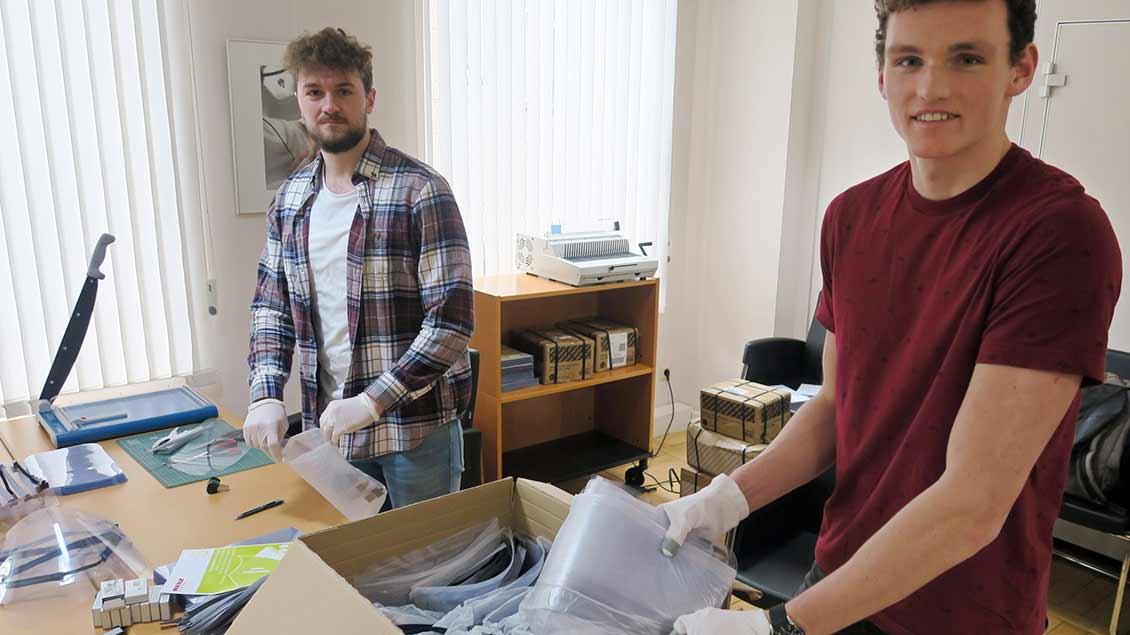 """Leon Paulat, Dr. Heinz-Georg Kaysers und Jos Grootens (von links) in ihrer """"Mini-Fabrik"""", in der sie gemeinsam mit Claudio Arnold (nicht im Bild) die Face-shields anfertigen. Alles, was sie dafür brauchen passt auf einen Schreibtisch und ist leicht zu besorgen."""