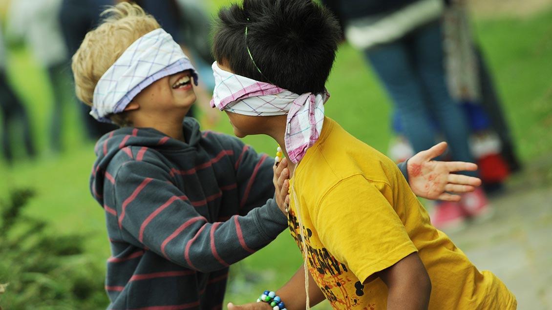 Zei Kinder spielen mit verbundenden Augen während einer Ferienfreizeit.