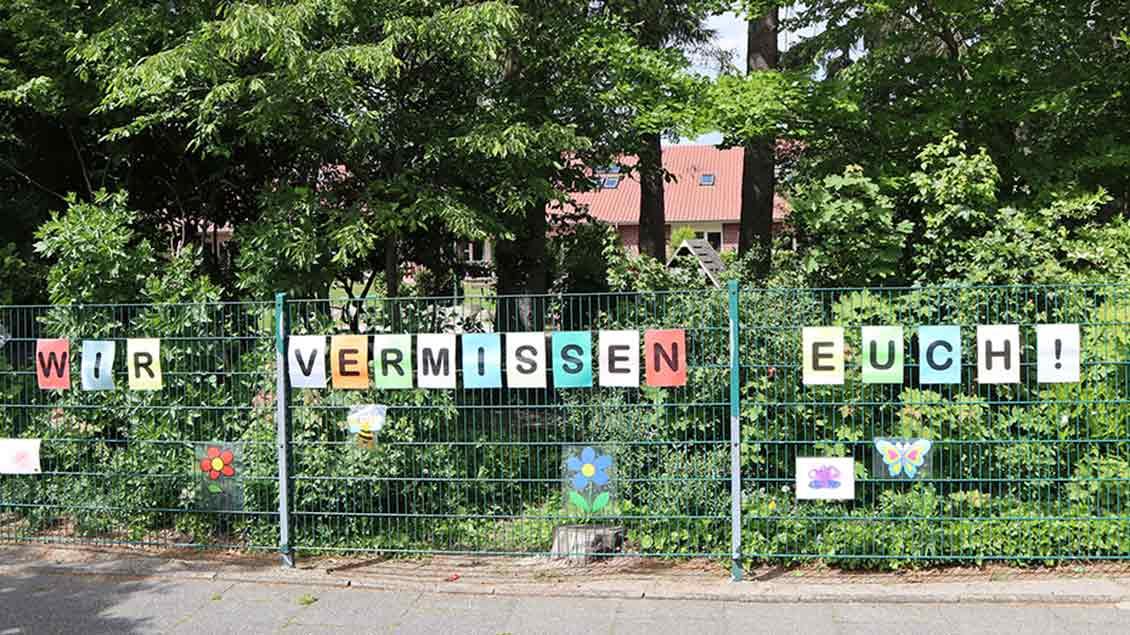 """Kindergartenzaun mit Aufschrift """"Wir vermissen Euch"""""""