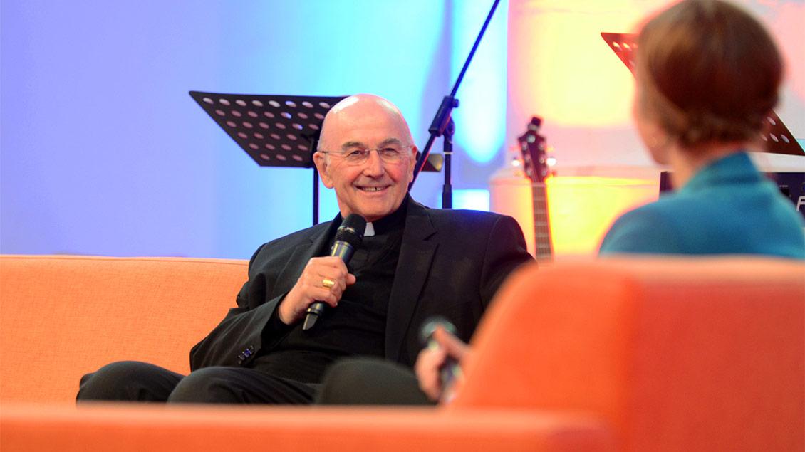 Bischof Felix Genn sitzt in der Jugendkirche in Münster auf einem Sofa und spricht in ein Mikrofon. Foto: pd