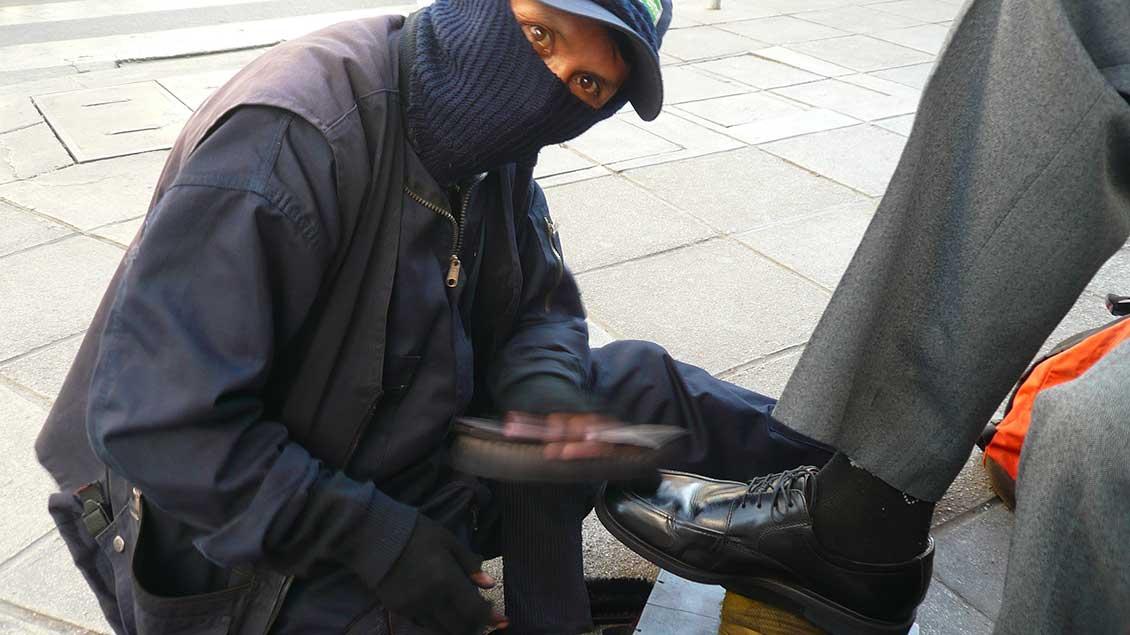 Ein Schuhputzer bei der Arbeit.