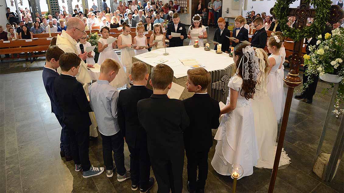 Um einen Altar stehen Erstkommunionkinder mit dem Priester und halten sich an den Händen.