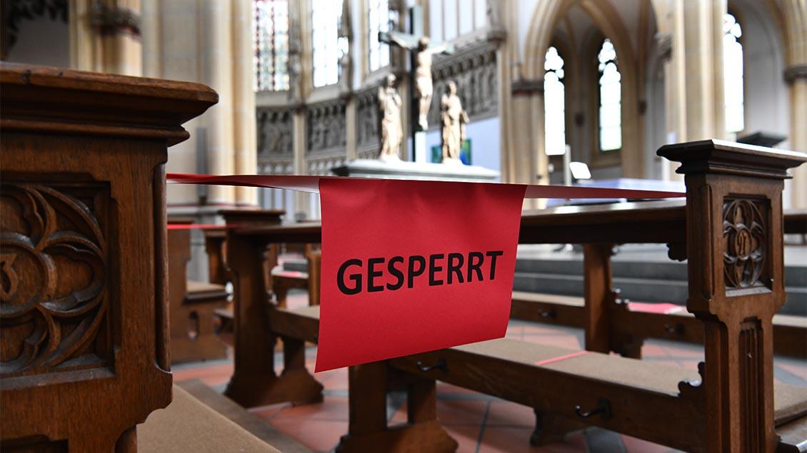 """Zwischen zwei Kirchenbänken hängt ein Schild mit der Aufschrift """"gesperrt""""."""