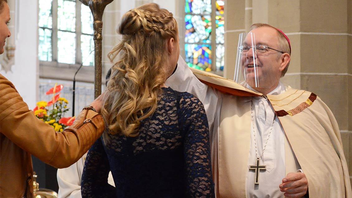 Weihbischof Christoph Hegge trägt einen Gesichtsschutz und spendet einer jungen Frau den Segen.