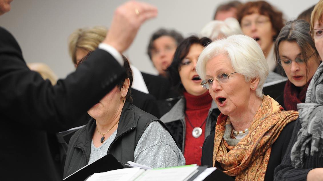 Eine Frau in einem Chor schaut zum Dirigenten und singt.