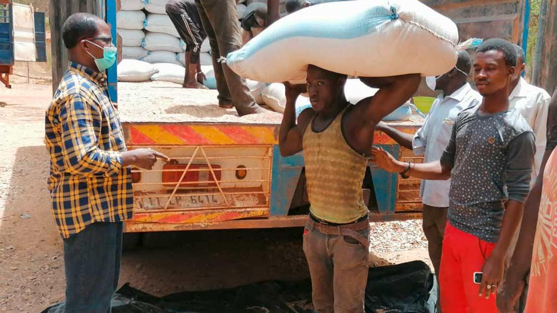 Afrikaner laden Hilfsgüter von einem Kleinlaster.
