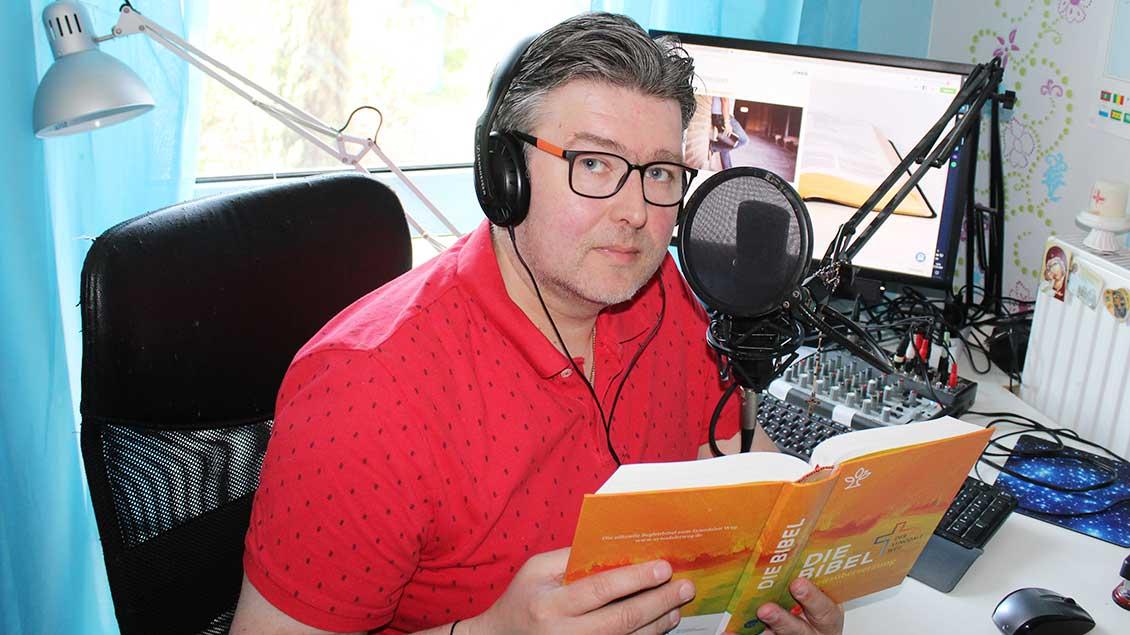 Oliver Kelch mit Bibel und Mikrofon.