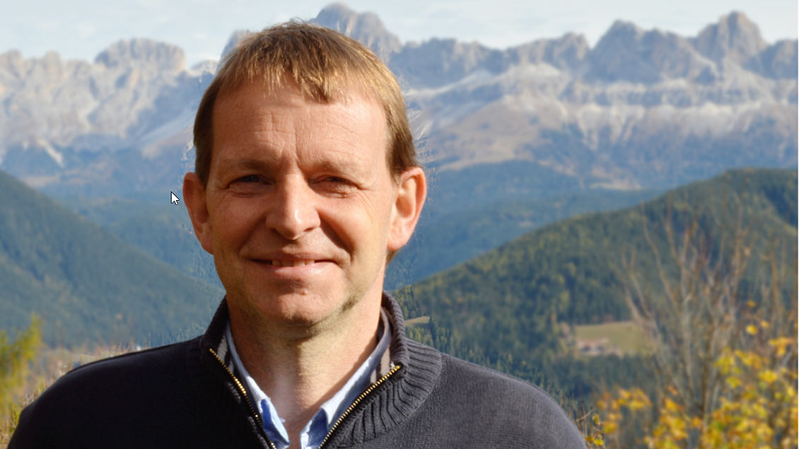 Andreas Rehm steht vor einem Bergpanorama und lächelt.