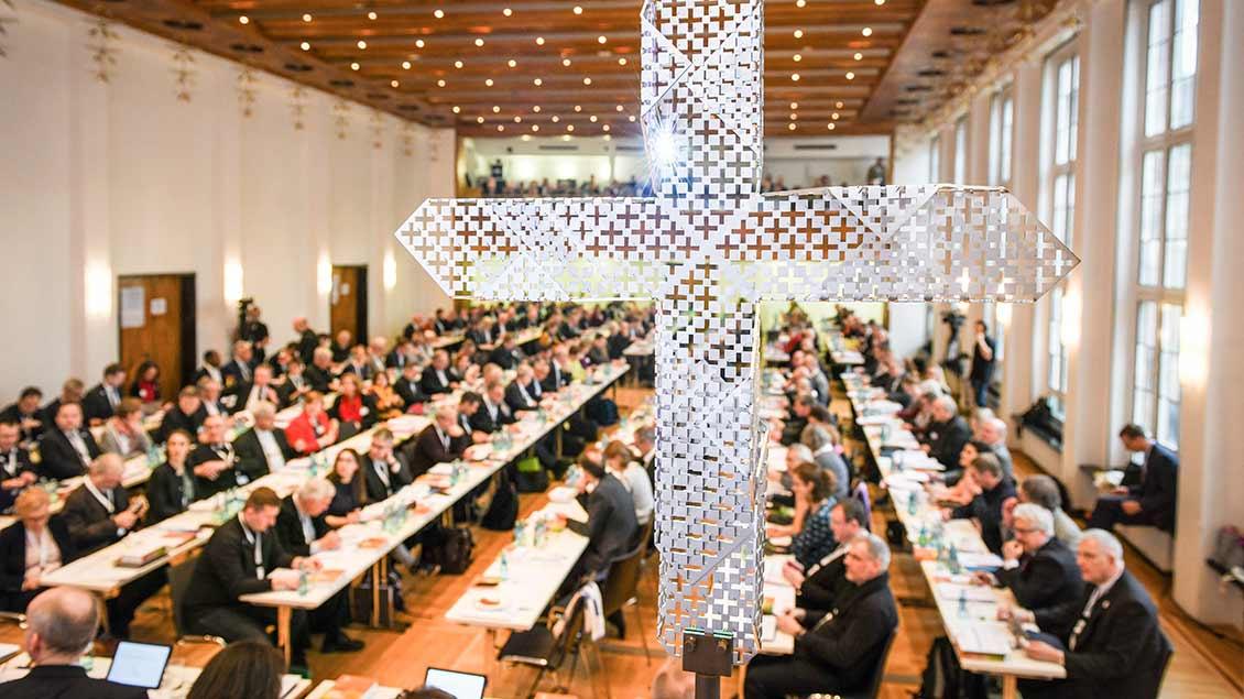 Blick durch ein gelochtes Metallkreuz auf die Teilnehmer an langen Tischen bei den Beratungen der Synodalversammlung am 31. Januar 2020 im Dominikanerkloster in Frankfurt.