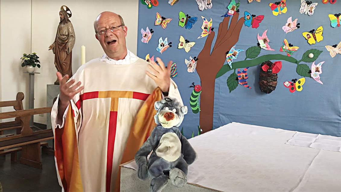 Pfarrer Christoph Winkeler steht in einer Kirche und hat eine Stoffpuppe von Balou dem Bären aus dem Dschungelbuch dabei.