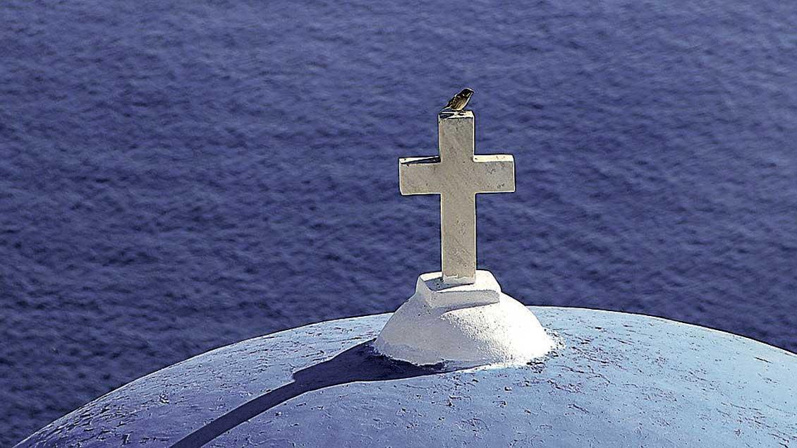 Ein Spatz auf einem Kirchturmkreuz