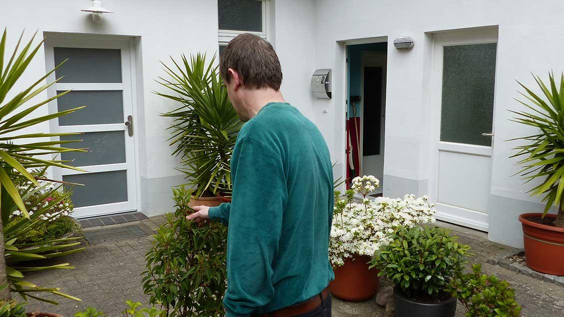 Vor dem Eingang der Klause in Jever: Bruder Gereon bewundert bei einem Spaziergang die Blumenpracht seines Nachbarn.Der Eremit möchte nicht im Porträt fotografiert werden. | Foto: Franz Josef Scheeben