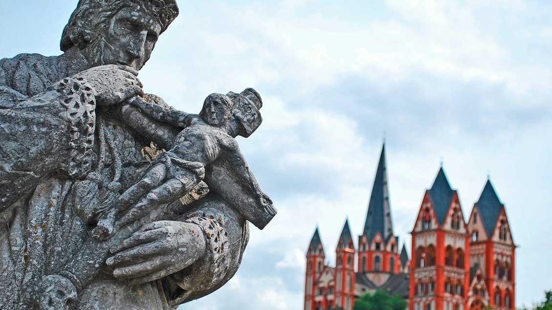 Der Limburger Dom von der Alten Lahnbrücke aus fotografiert. Im Vordergrund die Statue des Heiligen Nepomuk mit dem gekreuzigten Christus im Arm.
