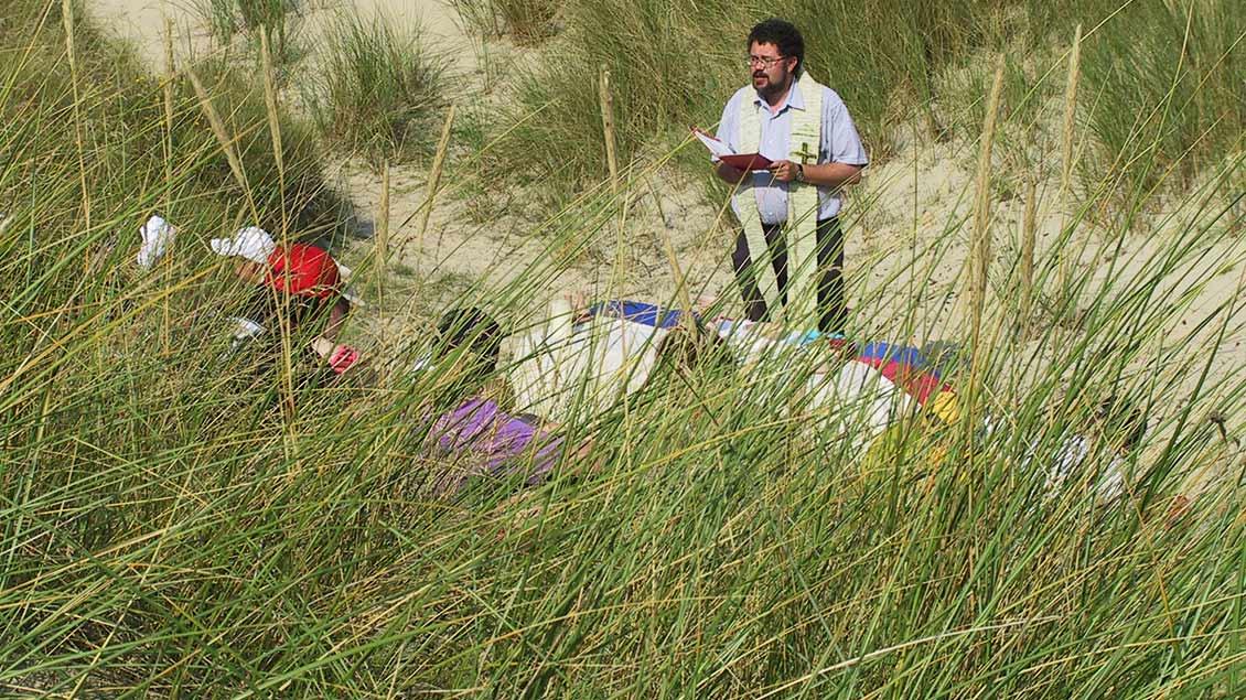 Ein Priester feiert in den Dünen ein Gottesdienst mit Kindern.