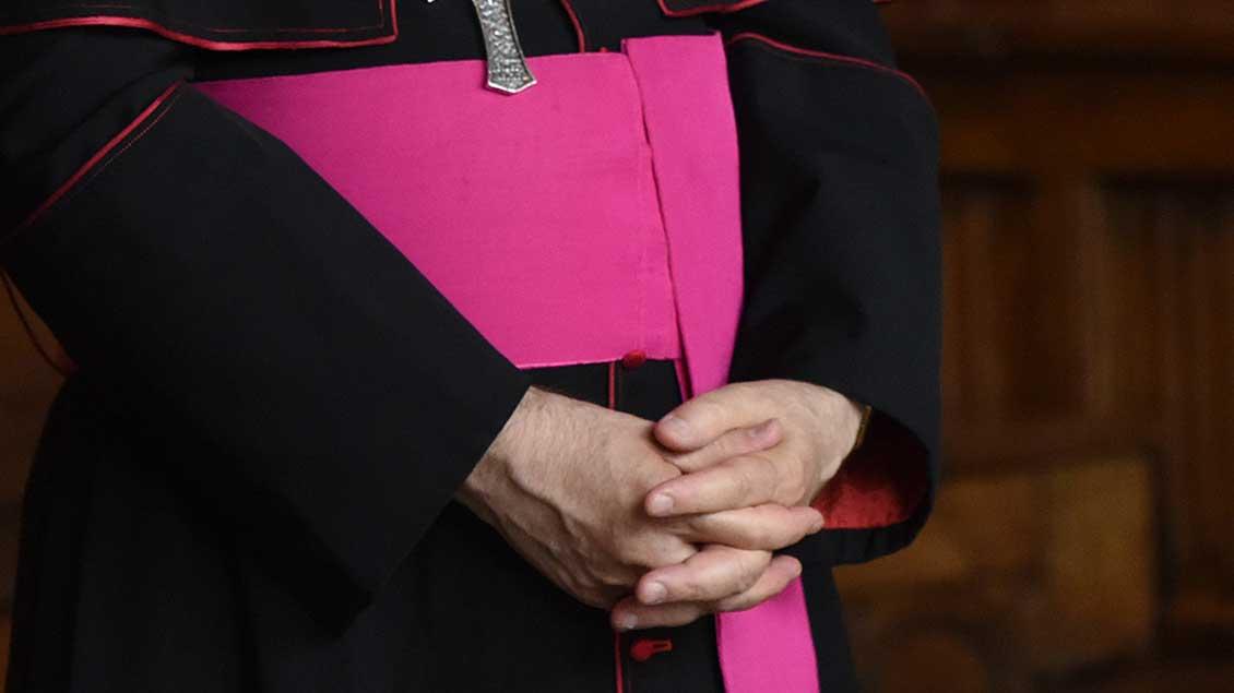 Bischof faltet die Hände vor der Soutane.