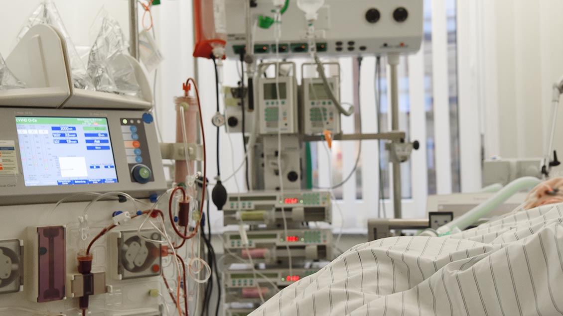 In einem Krankenbett einer Intensivstation liegt ein Patient.