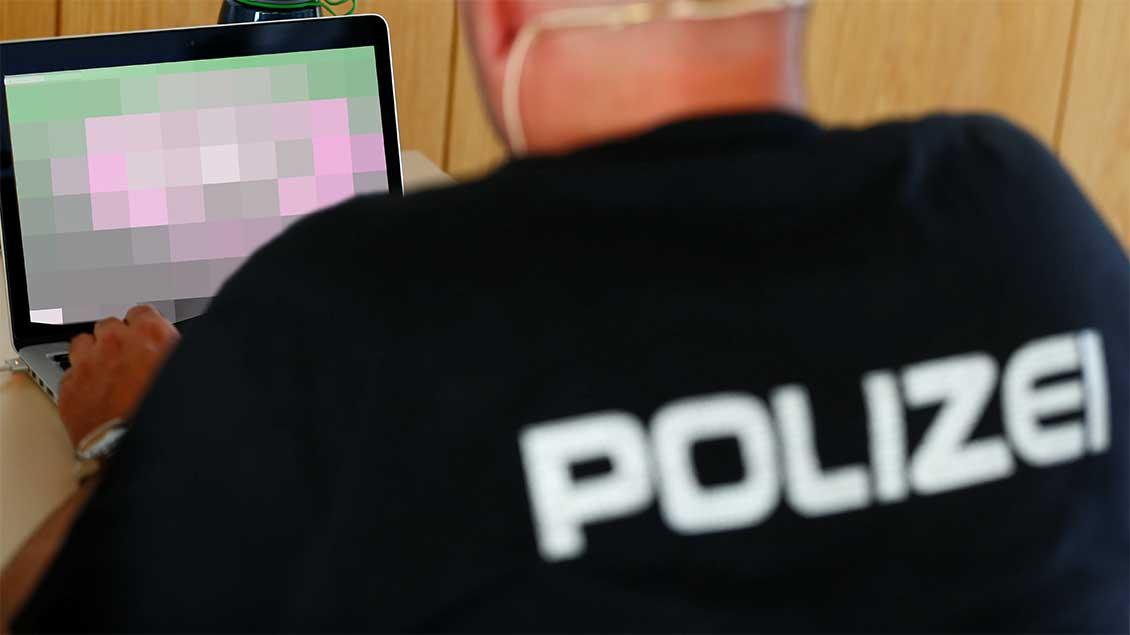 Polizist vor einem Laptop.
