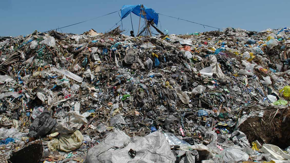 Ein Kind sitzt in einer einfachen Bahausung auf einer Müllhalde auf den Philippinen
