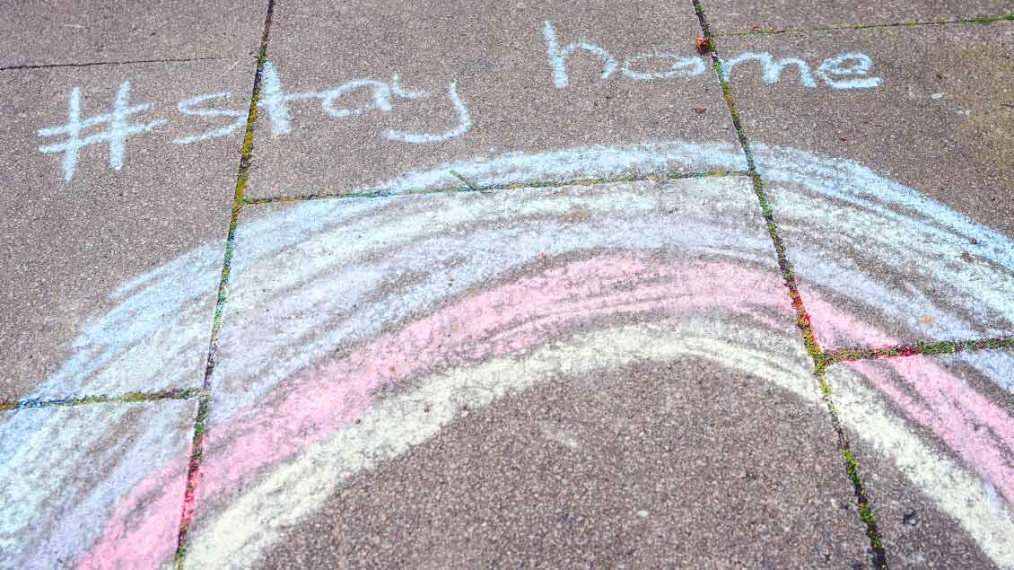 """Auf einem Bürgersteig ist mit Kreide ein Regenbogen aufgemalt. Darüber steht """"#stay home"""""""
