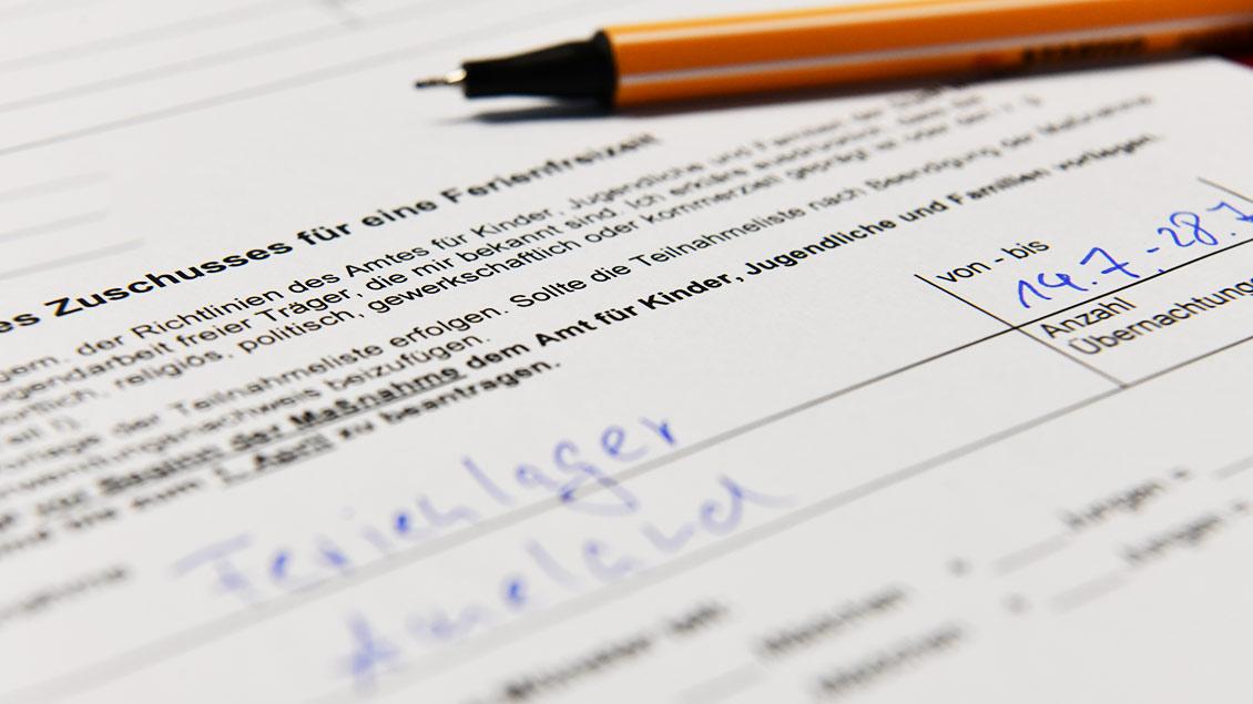 Aufeinem Antrag auf Fördergelder für Ferienfreizeiten liegt ein Stift. Foto: Michael Bönte