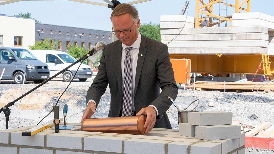 "Generalvikar Winterkamp versenkte die Zeitkapsel im ""Tita-Cory-Campus""."
