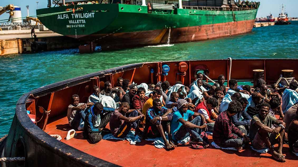 Migranten sitzen an Deck des Schiffes William Butler Yeats der irischen Marine bei dessen Ankunft im Hafen von Augusta (Sizilien) am 3. September 2017.