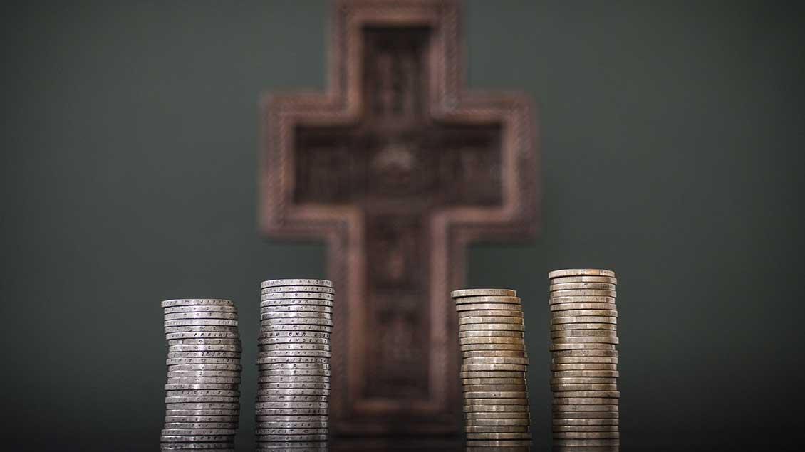 Symbolbild mit Münzen vor einem Kreuz