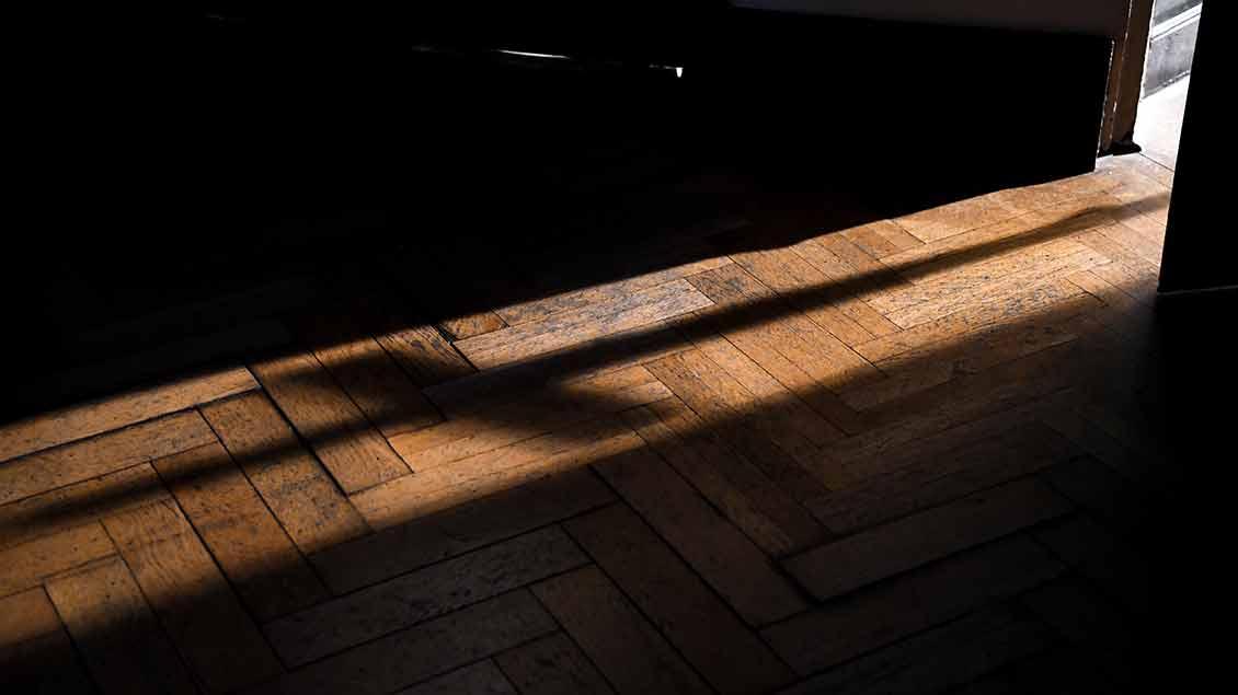 Schatten eines Kreuzes fällt durch Tür