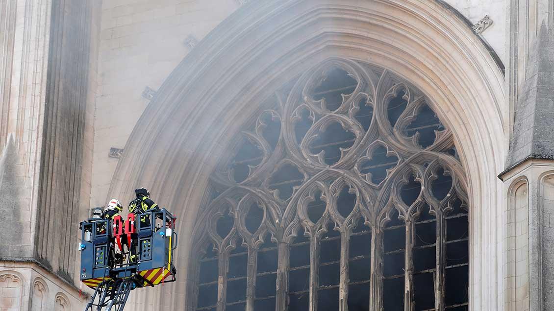 Feuerwehrleute vor einem Fenster der brennenden Kathedrale von Nantes