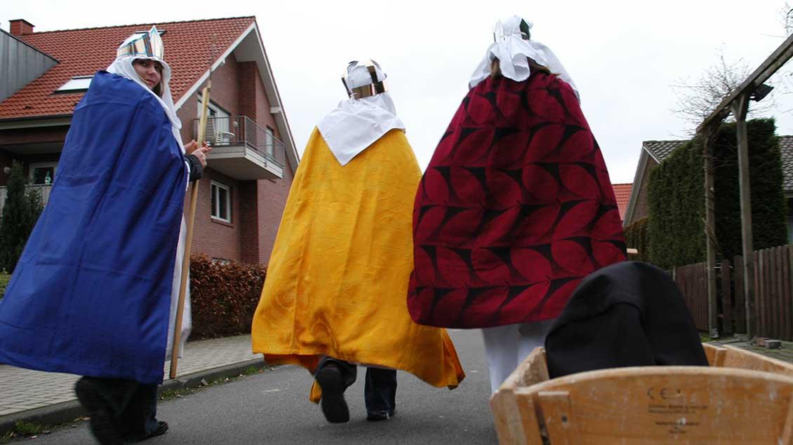Drei Sternsinger gehen eine Straße entlang.