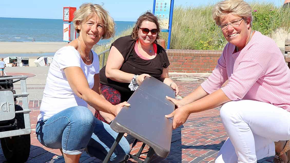 Anke Bartel, Sophia Maria Menner und Anne Nöcker (von links) bringen Sitzbänke zum Strand. | Foto: Michael Rottmann
