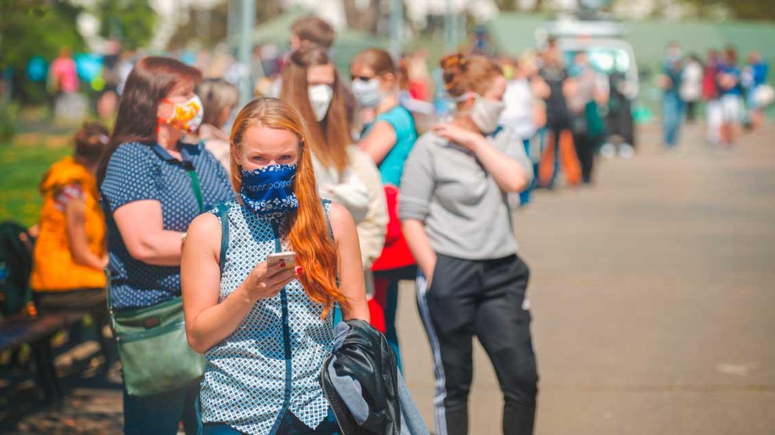 Menschen mit Masken in einer Schlange