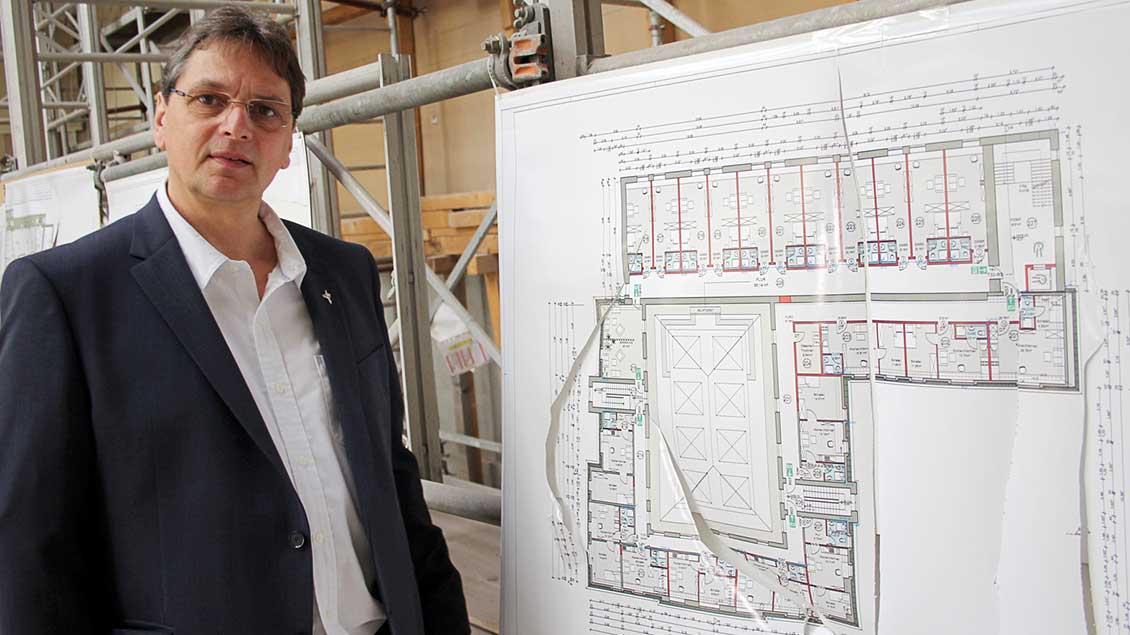 Caritasdirektor Michael van Meerbeck vor den Bauplänen.