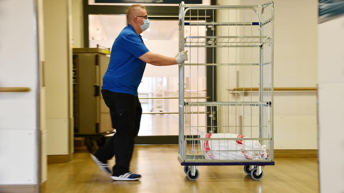 Patrick Onnebrink schiebt einen Wäschewagen über den Gang des St.-Marien-Hospitals in Lüdinghausen.