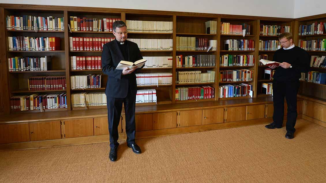 Priester in einer Bibliothek
