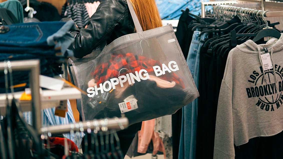 """Frau mit einer großen Einkaufstasche mit der Aufschrift """"Shopping Bag"""" in einem Bekleidungsgeschäft."""