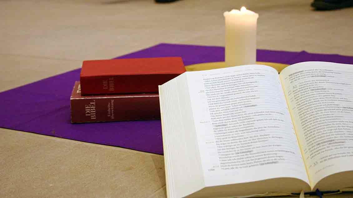 Eine Bibel im Kerzenlicht.