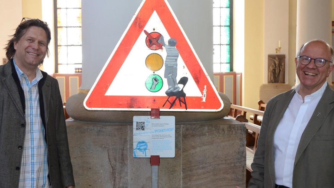 Pastoralreferent Christoph Moormann hat die Schilder-Ausstellung zur neuen BDKJ-Bibel in die Ibbenbürener Pfarrkirche St. Mauritius geholt. Pfarrer Stefan Dördelmann (rechts) freut sich über dieses Angebot.