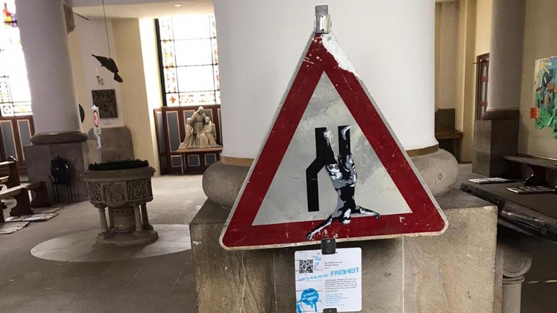 In die Freihheit fällt die Figur auf diesem Schild.