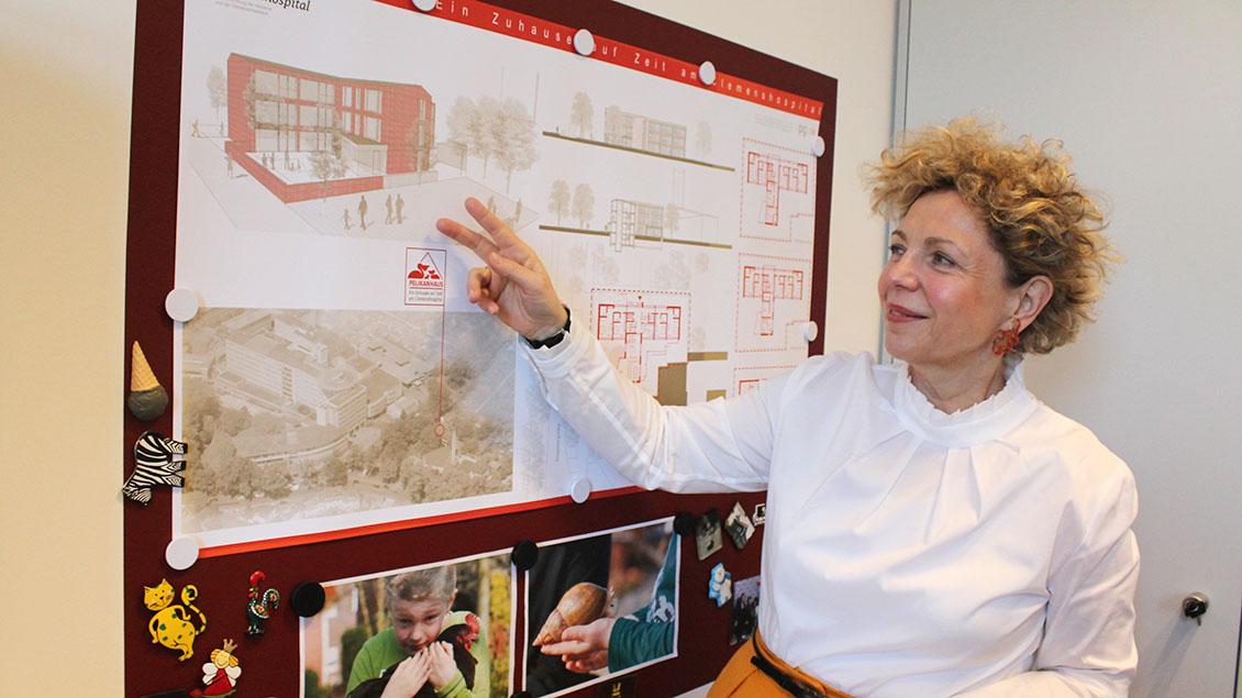 Eine Frau zeigt auf den Plan eines Hauses.
